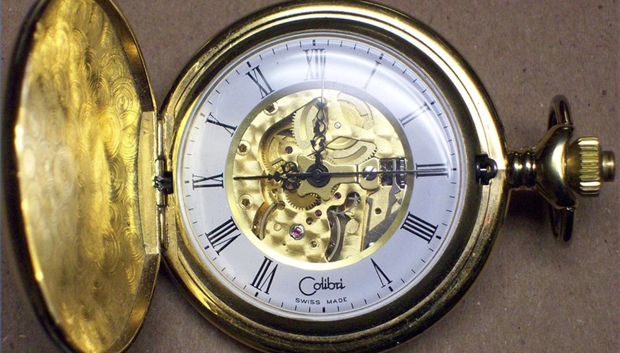 A pocket watch showing the movement inside.