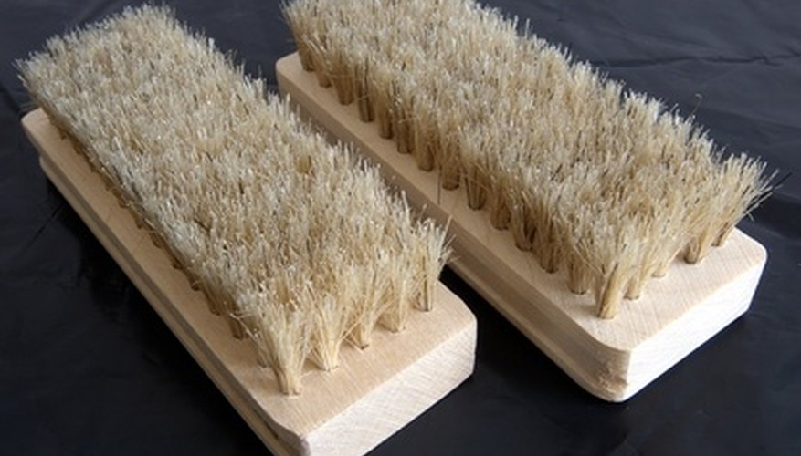A scrub brush will help to loosen debris from the surface of the concrete.