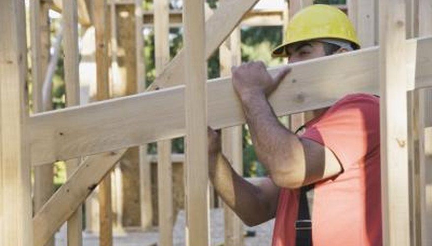 A man builds the frame of a house.
