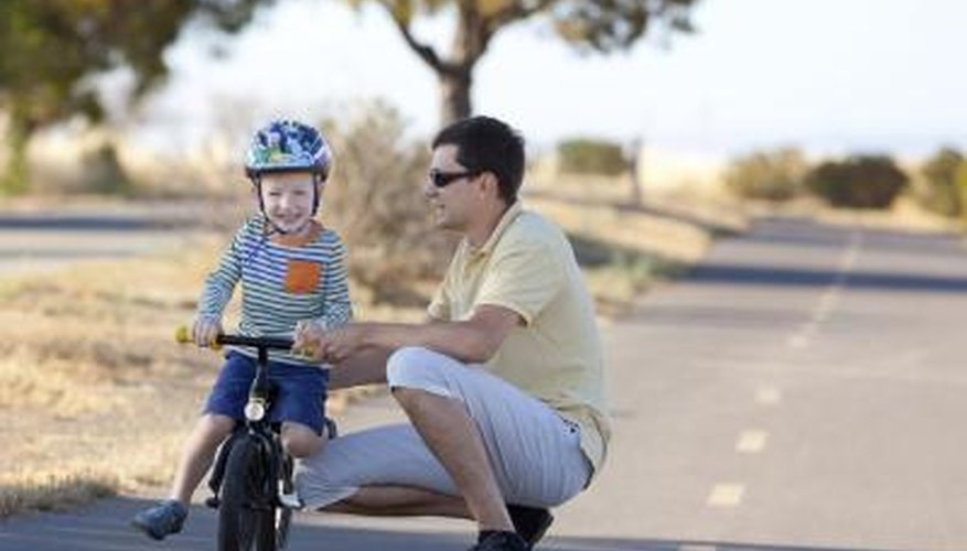Boy with father learning to ride bicycle