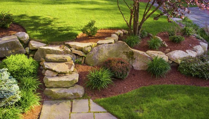 A rock garden with mulch highlights a slope in the front yard.