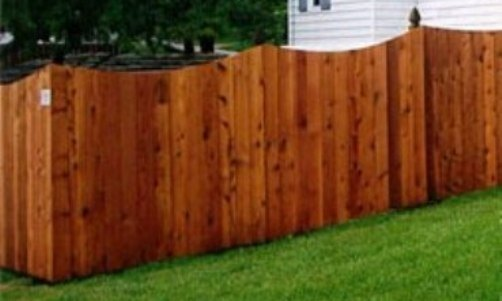 A decorative scalloped cedar fence design.