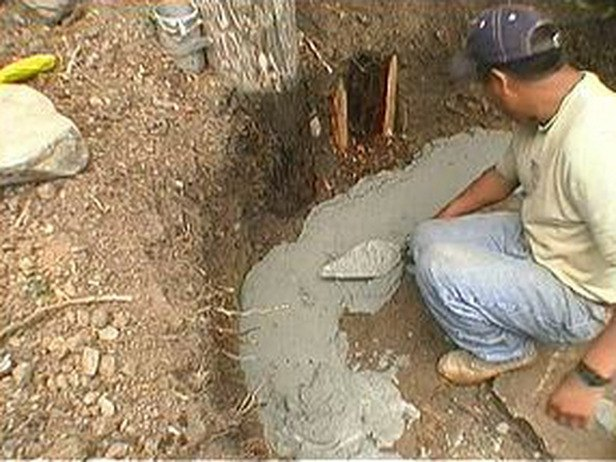 Mortar is spread into a trench for a curved bench.