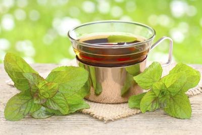 A cup of peppermint tea with peppermint leaves.