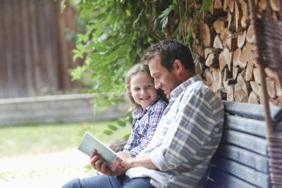 A father shares a book with his daughter on a bench at a cabin.