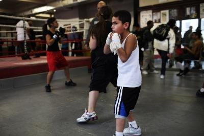 Boy practicing boxing in community gym