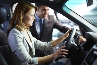 A woman sitting in the driver's seat of a new car with a salesman standing next to her