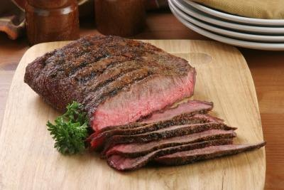 Sliced flank steak on cutting board.