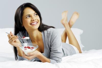 A woman is eating yogurt on her bed.
