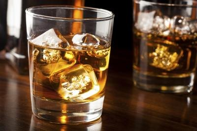 A glass with whiskey on the rocks.