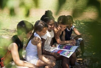 A group of children look at a plant identification book outside.