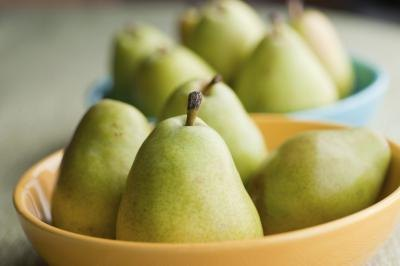 Put two to three fresh pears into a brown paper bag. Put in one ripe banana.