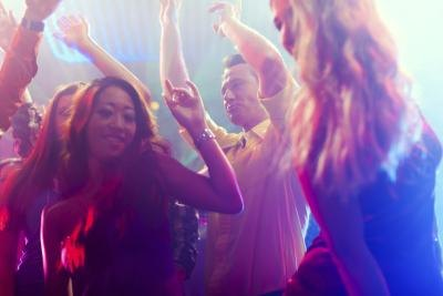Revelers dancing on a nightclub dance floor.