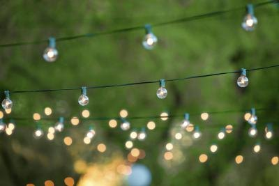 An outdoor area is decorated with gorgeous hanging lights