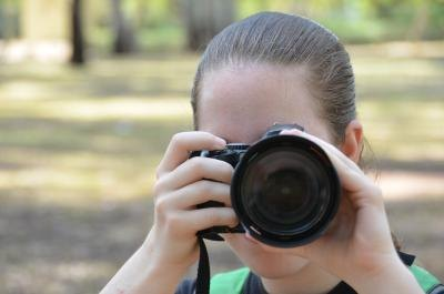 Teen girl takes photo with digital camera