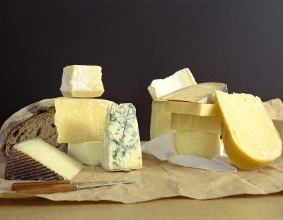 A board with a variety of cheeses.