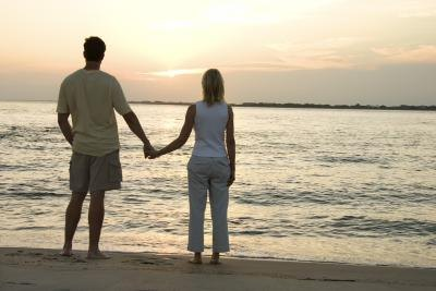 A couple holds hands and watches the sunset.