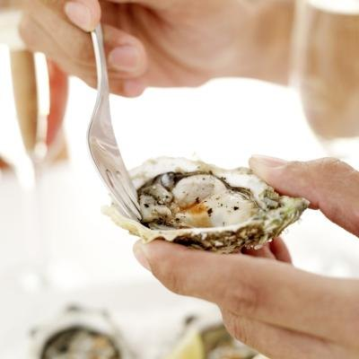 A close-up of a woman using a fork to loosen a raw oyster from the shell