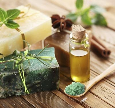 Natural soaps next to a bottle of essential oil and herbs