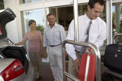 A hotel employee assists guests with their luggage.