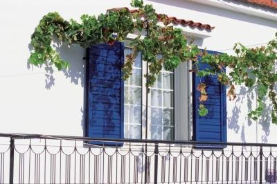 A window with bright blue shutters in Greece.