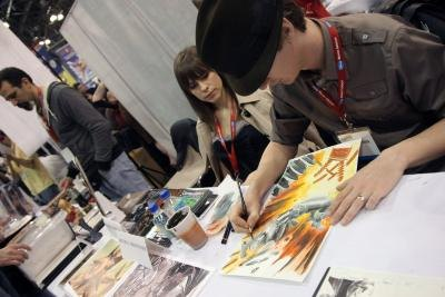 A comic book artist works on a illustration at New York ComicCon