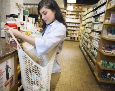 A woman fills a reusable bag with groceries at the check out.
