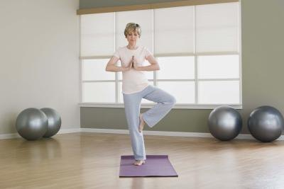 A woman balances on one foot during a yoga pose.