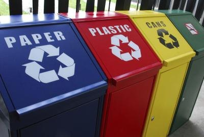 Four colorful recycling bins lined up by category outside.