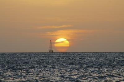 The silhouette of an oil rig on the horizon at sunset.