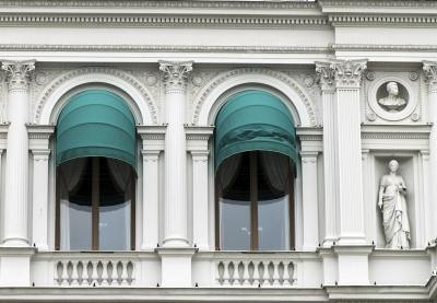 Awnings over two windows and a balcony.