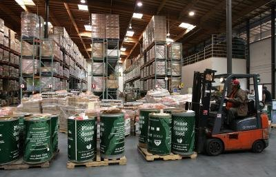 Forklift operator lifting barrels of donated food at San Francisco food bank.