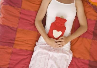 Woman with gastritis using a hot water bottle.