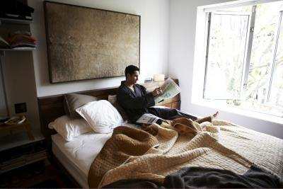 Man reading a newspaper in bed.