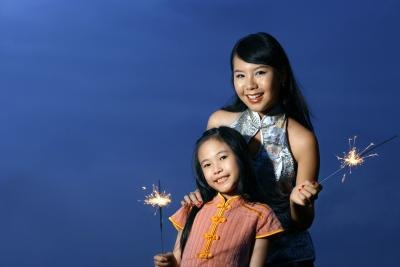 Mother supervising daughter with sparkler