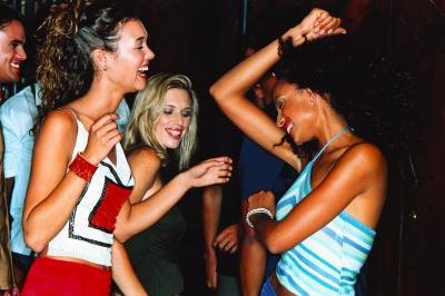 Three young women dancing together at a club.