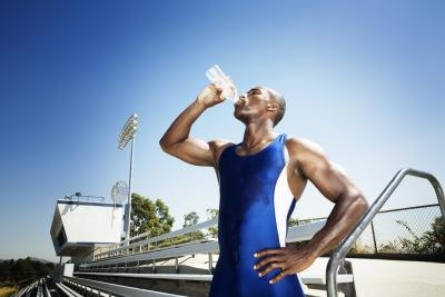 Young male athlete drinking water