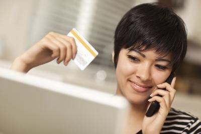 Woman on telephone holding credit card