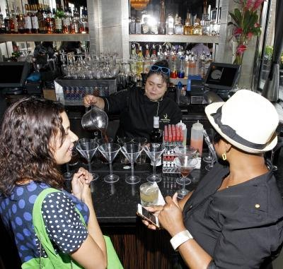 Female bartender pours drinks and talks with guests