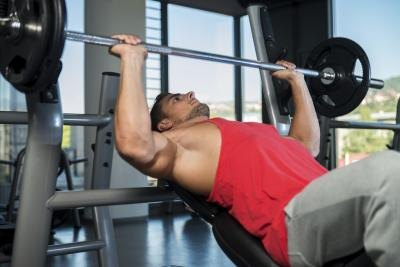 A man performs a bench press work out in a weight room.