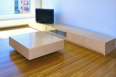 A living room has been cleared so the tables and credenzas can be used for seating and food placement