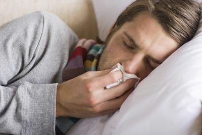 Man blowing nose in bed