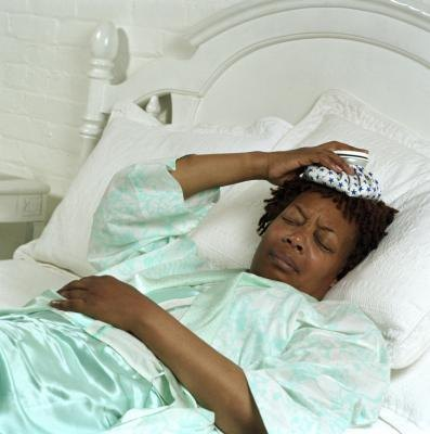 Woman in bed with head pain