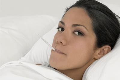 Young woman in bed with thermometer in mouth.