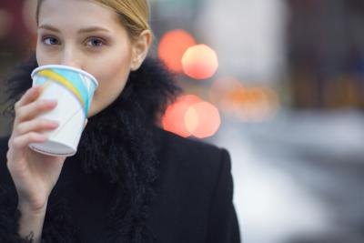 woman drinking from paper cup on sidewalk