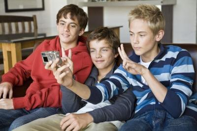 Teenage boys taking photo on couch