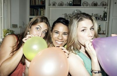 girls blowing up balloons with air