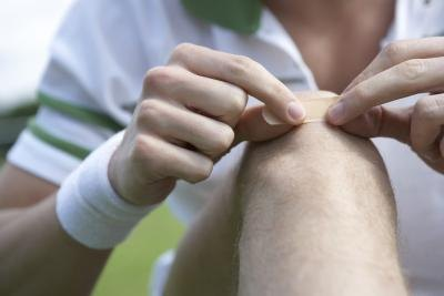 A tennis player adheres a bandage to his knee.