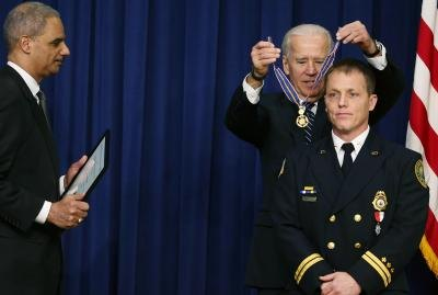 Firefighter in dress uniform receiving an award.