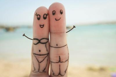 Ink on two fingers portrays a happy couple on the beach.